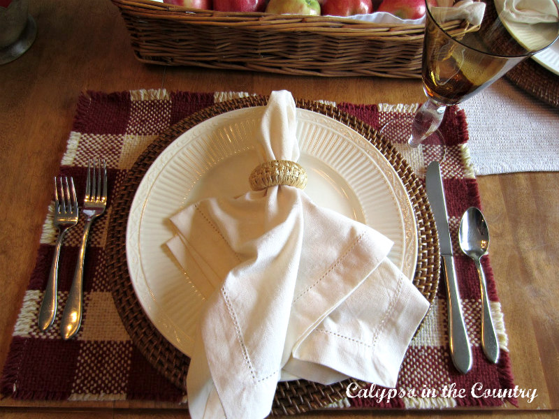 fall place setting with white napkin and red and white buffalo checked place mat