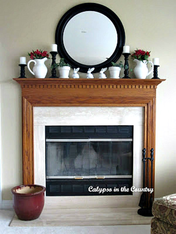 oak fireplace mantel with round mirror above