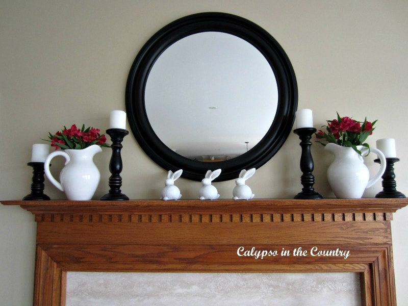 spring mantel with round mirror and white ceramic bunnies on mantel