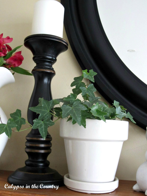 black candlestick and ivy in white flowerpot