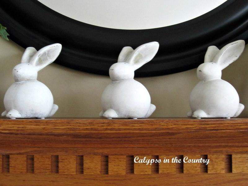 Three ceramic bunnies on fireplace mantel