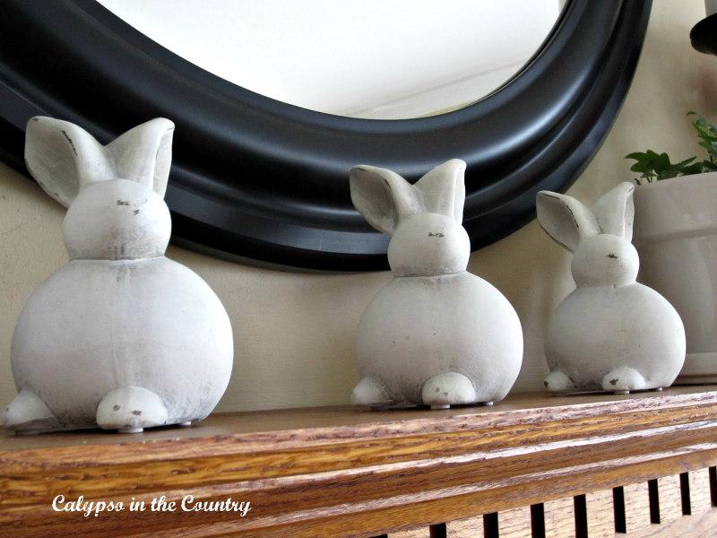 Three ceramic bunnies on spring mantel