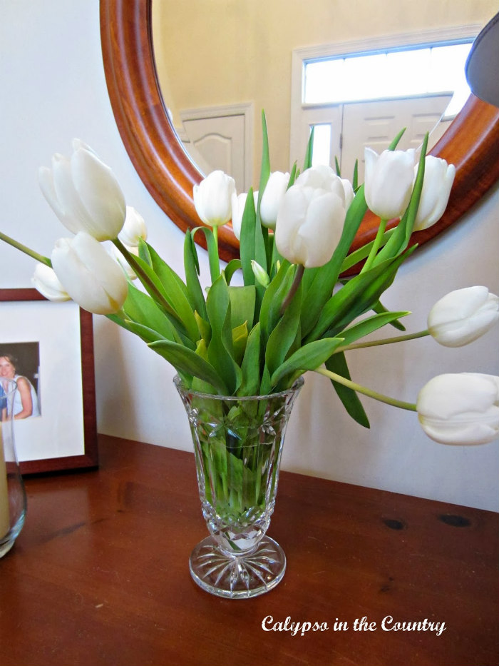 white tulips in crystal vase on foyer table
