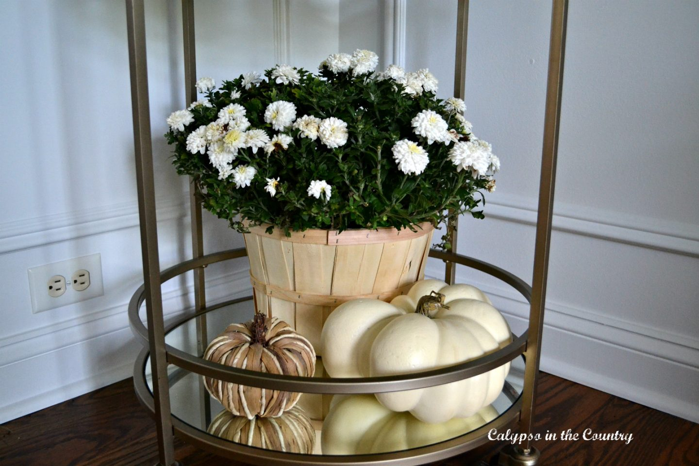 Gold bar cart decorated for fall using mums and pumpkins