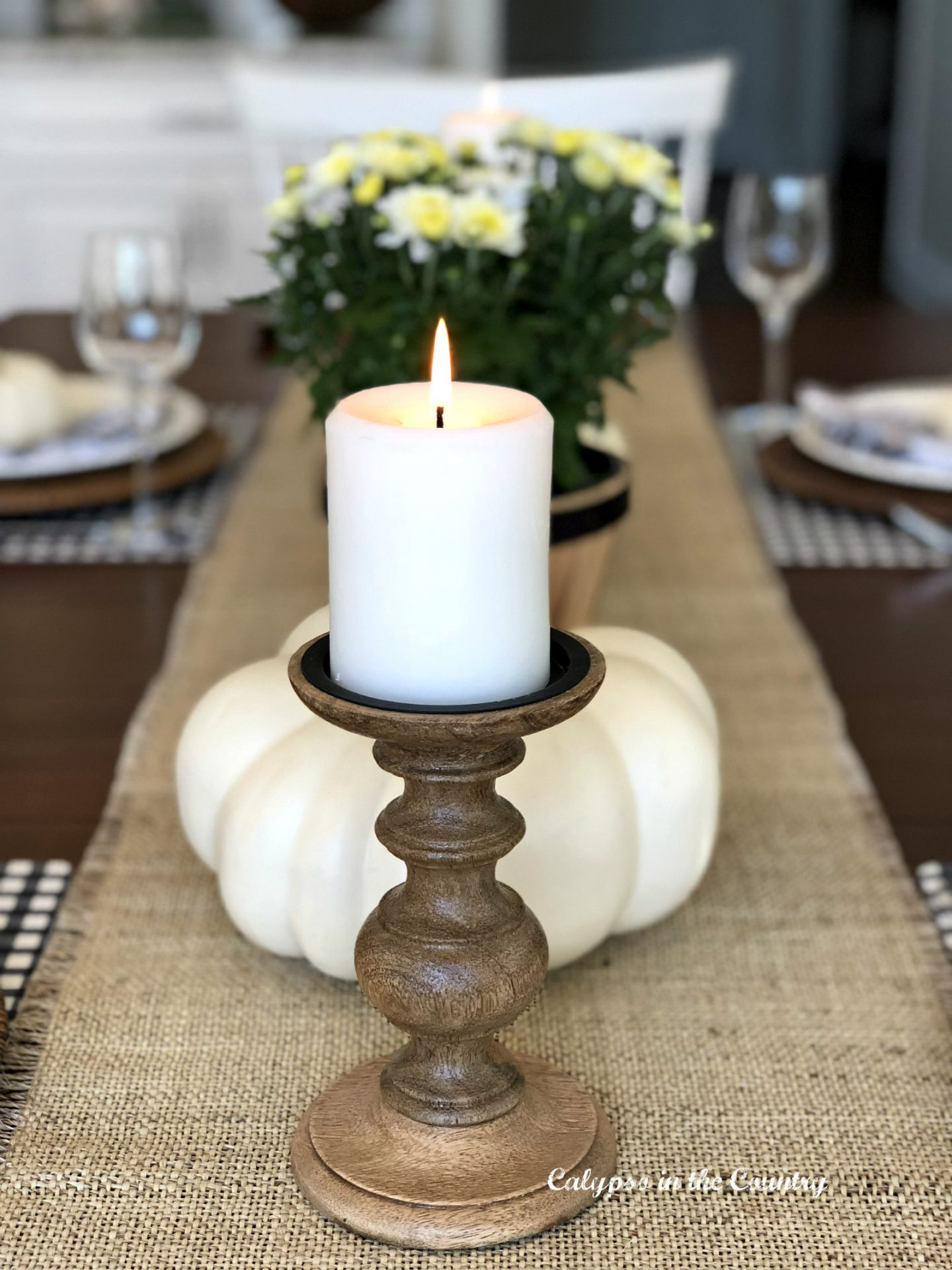Pumpkins and candles on rustic fall tablesetting