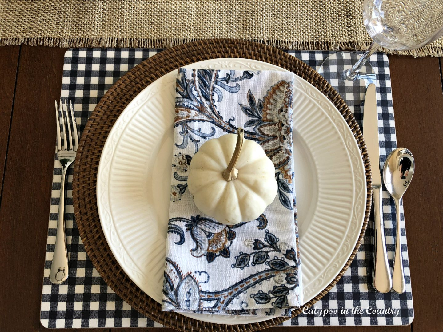 Fall table setting with blue and white checked placemat and white pumpkin