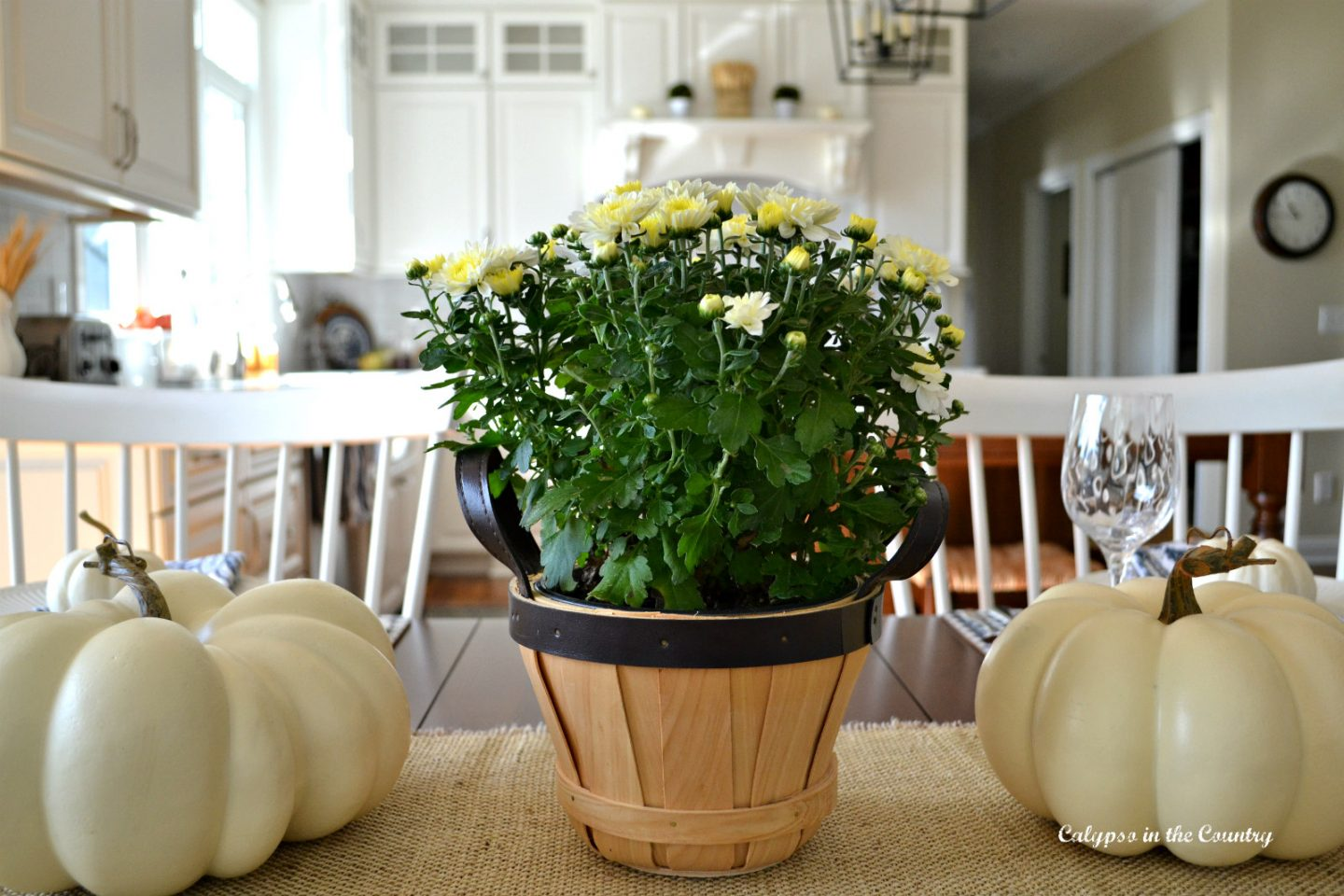 Farmhouse Kitchen table decorated with mums and white pumpkins