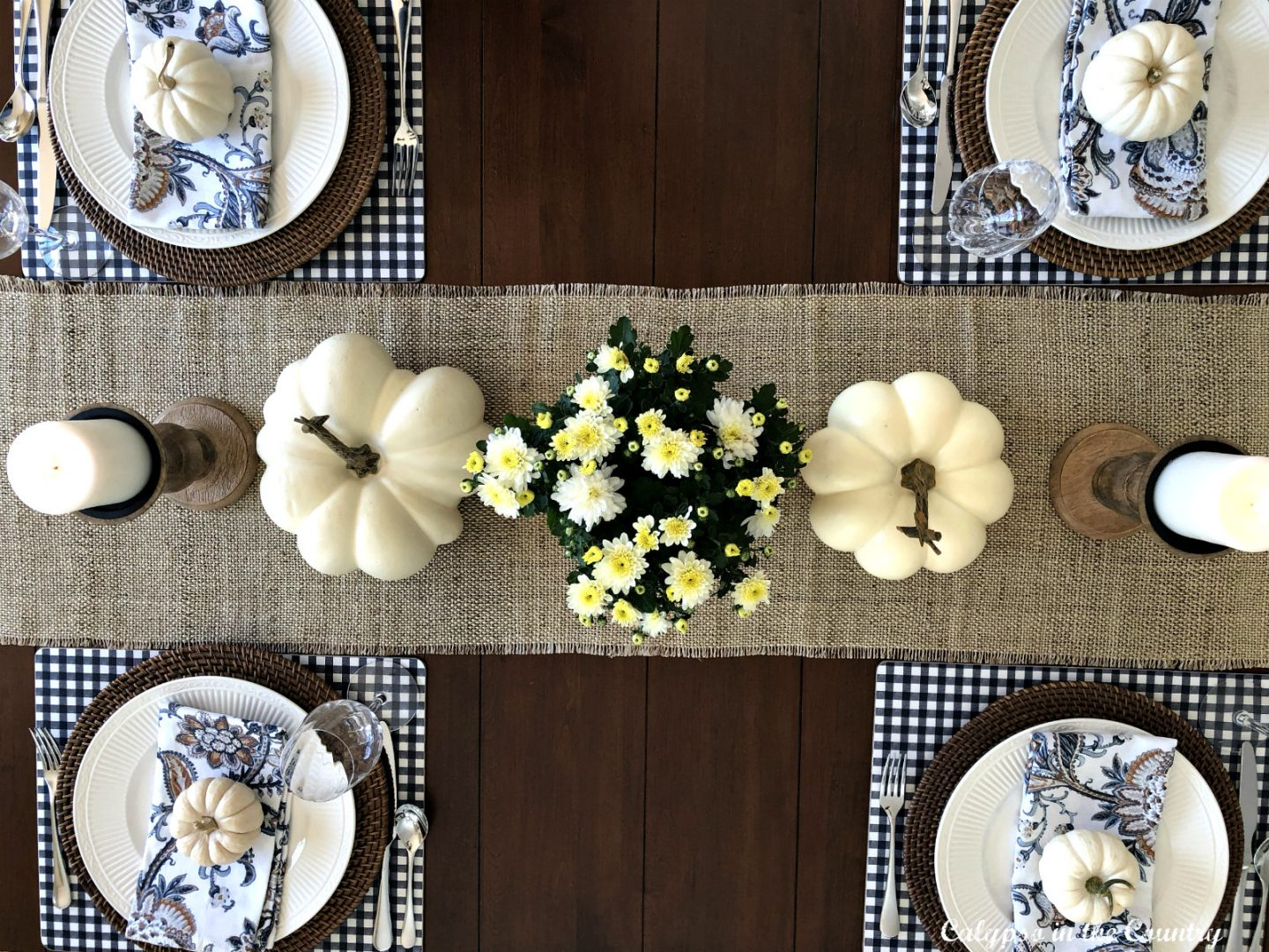 Top view of kitchen table decorated for fall with mums and white pumpkins