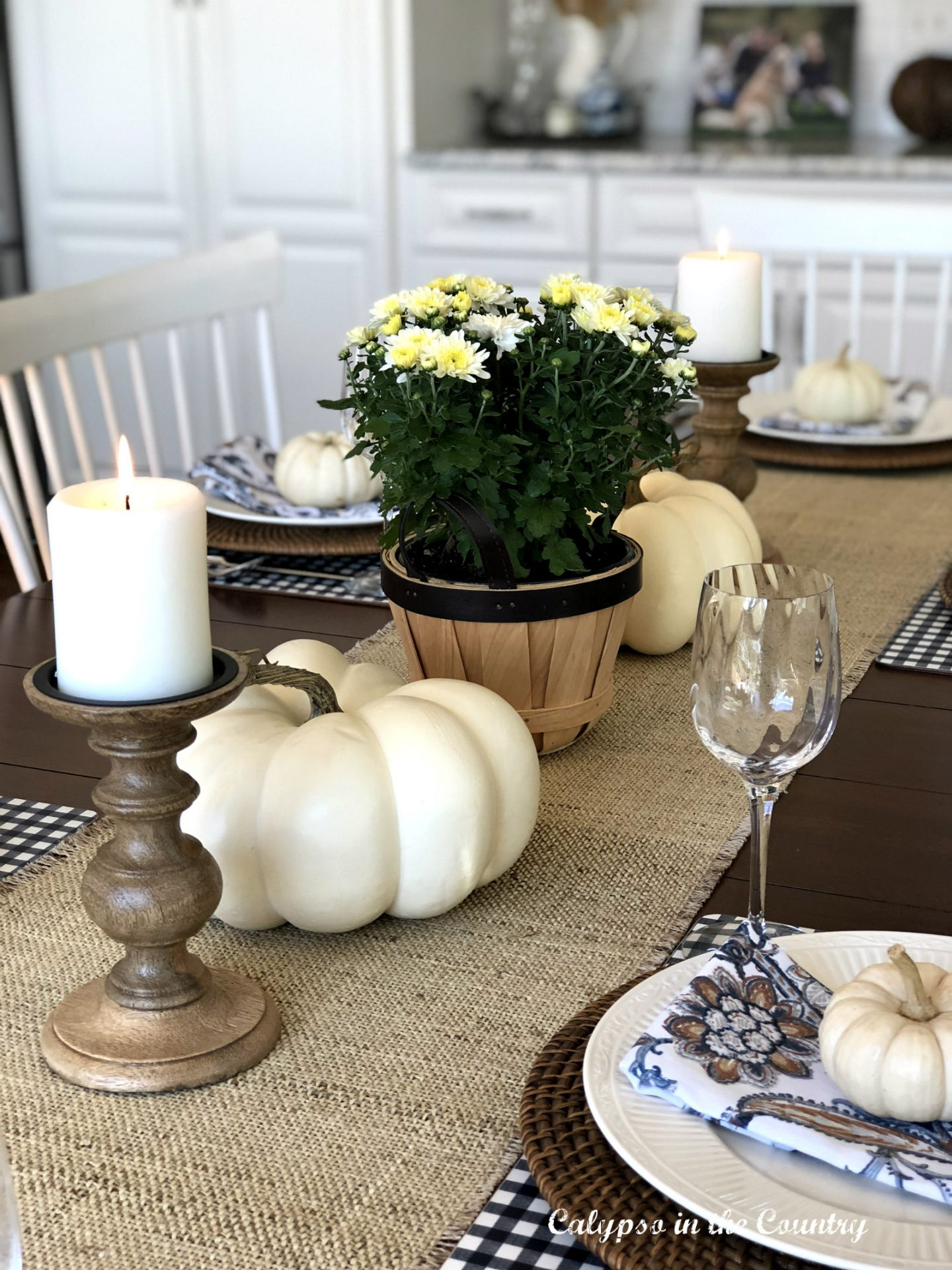 White pumpkins and mums on kitchen table for fall