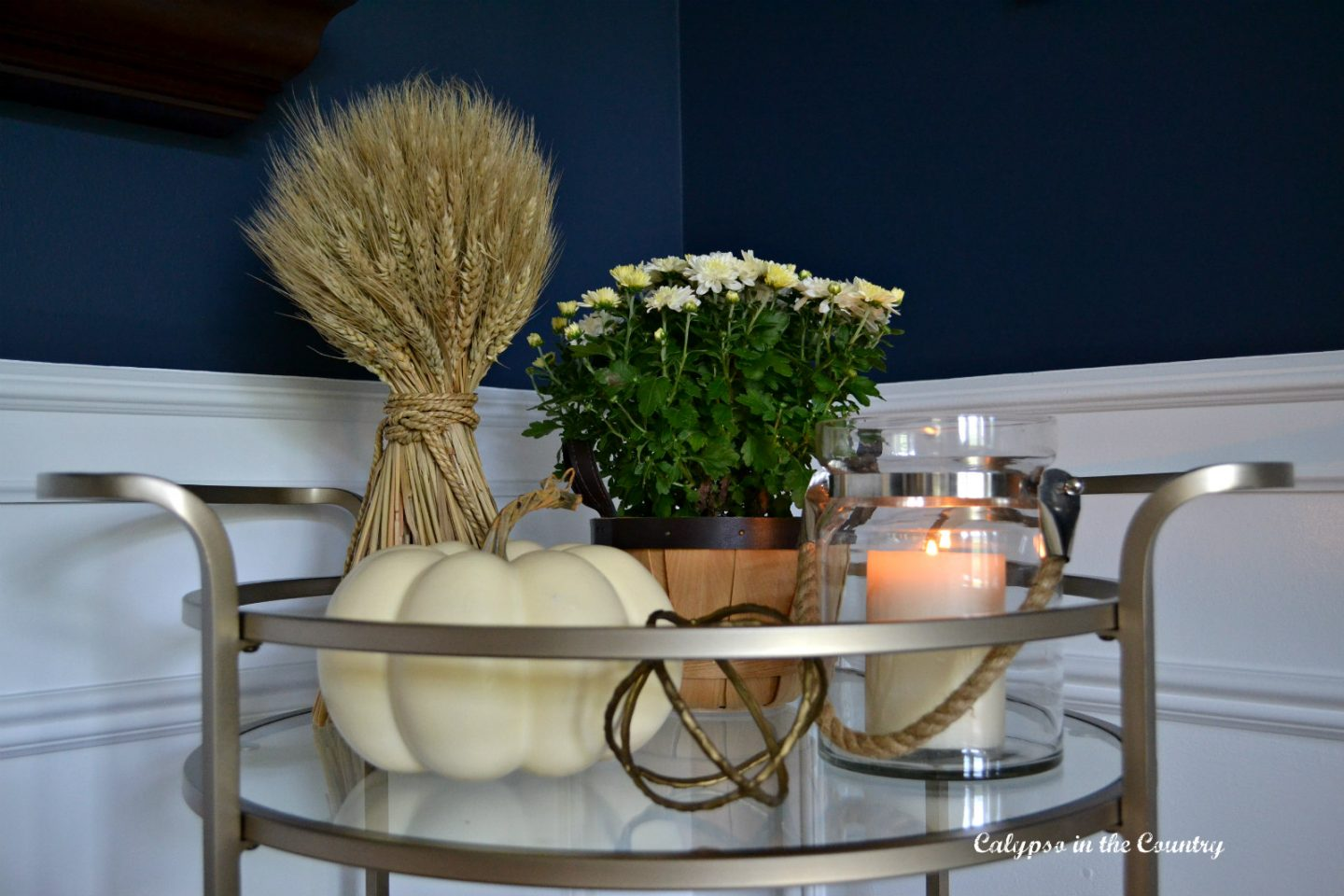 Bar cart styled with neutrals in a navy dining room - fall bar cart ideas