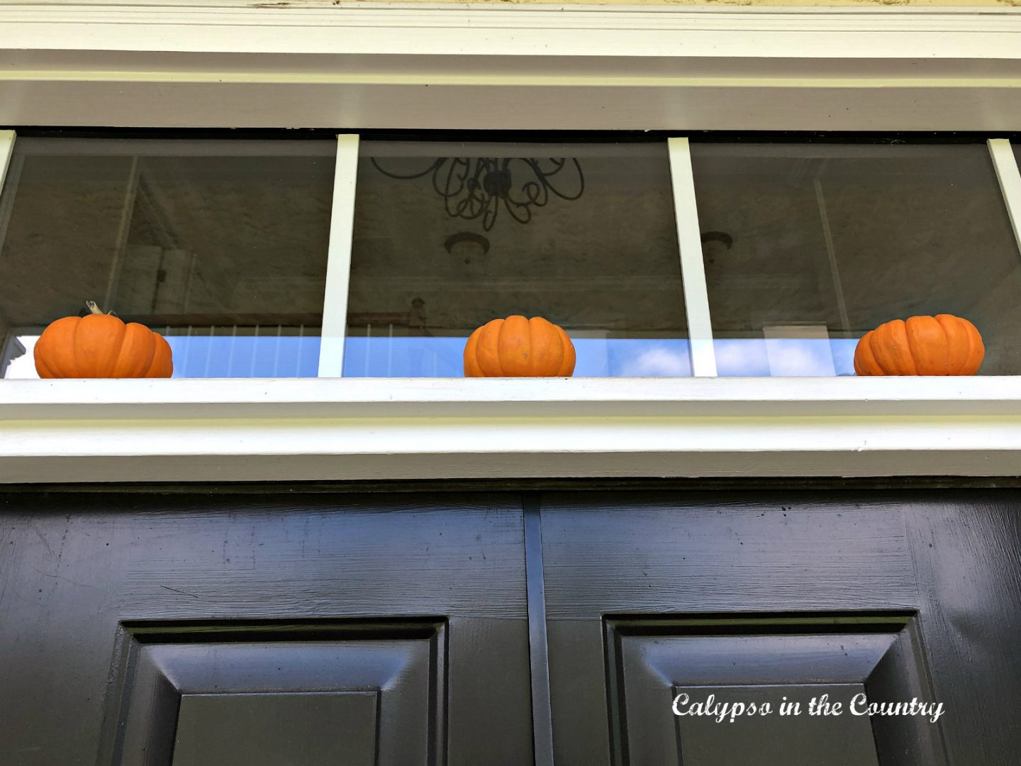 Mini pumpkins over front door