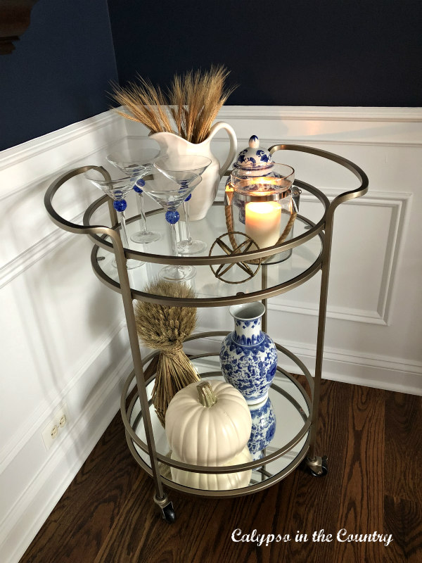 Round gold bar cart with blue and white fall accessories for Thanksgiving
