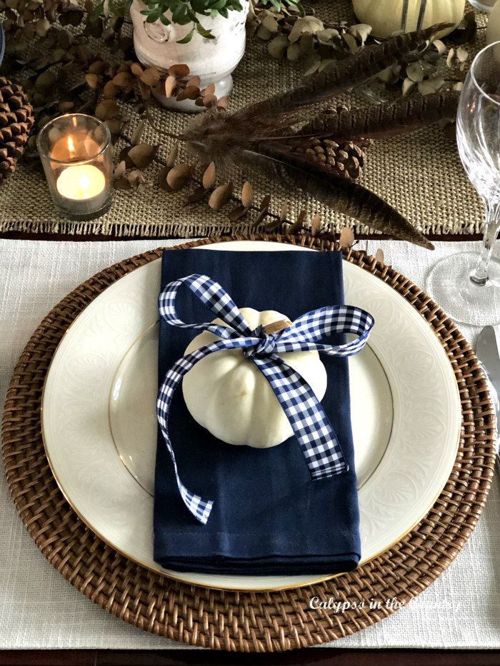 Festive Thanksgiving place setting with navy napkin and white pumpkin