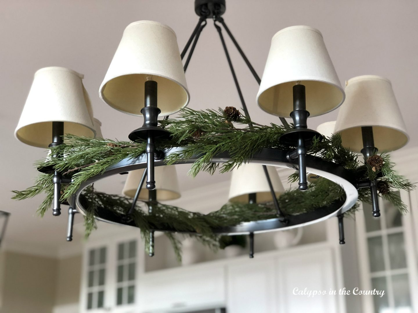 underside of chandelier with artificial greenery