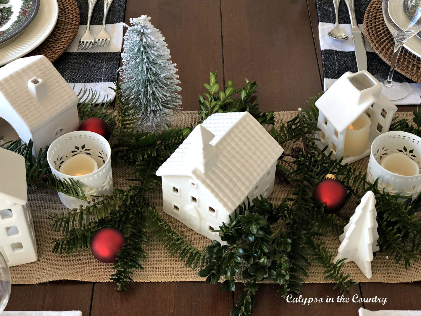 small white ceramic houses on table runner