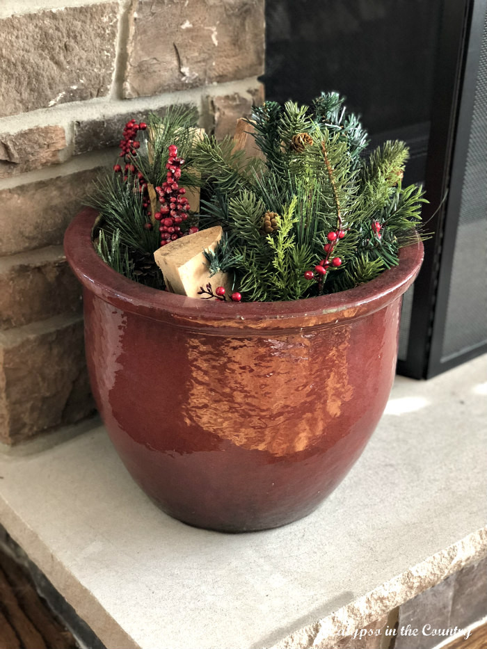red planter for wood and christmas greenery