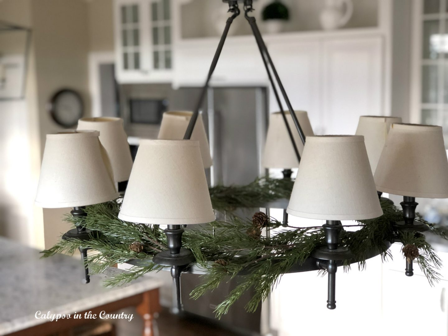 faux greenery on chandelier for christmas