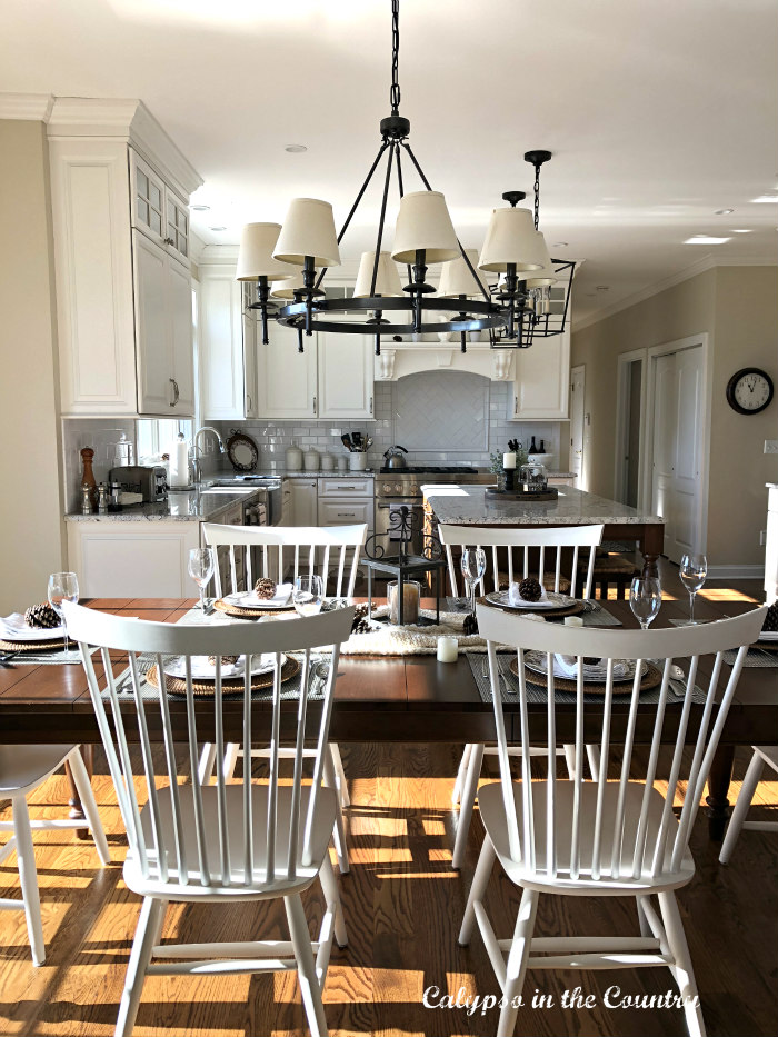 White Kitchen with brown table and white chairs - decorated for winter