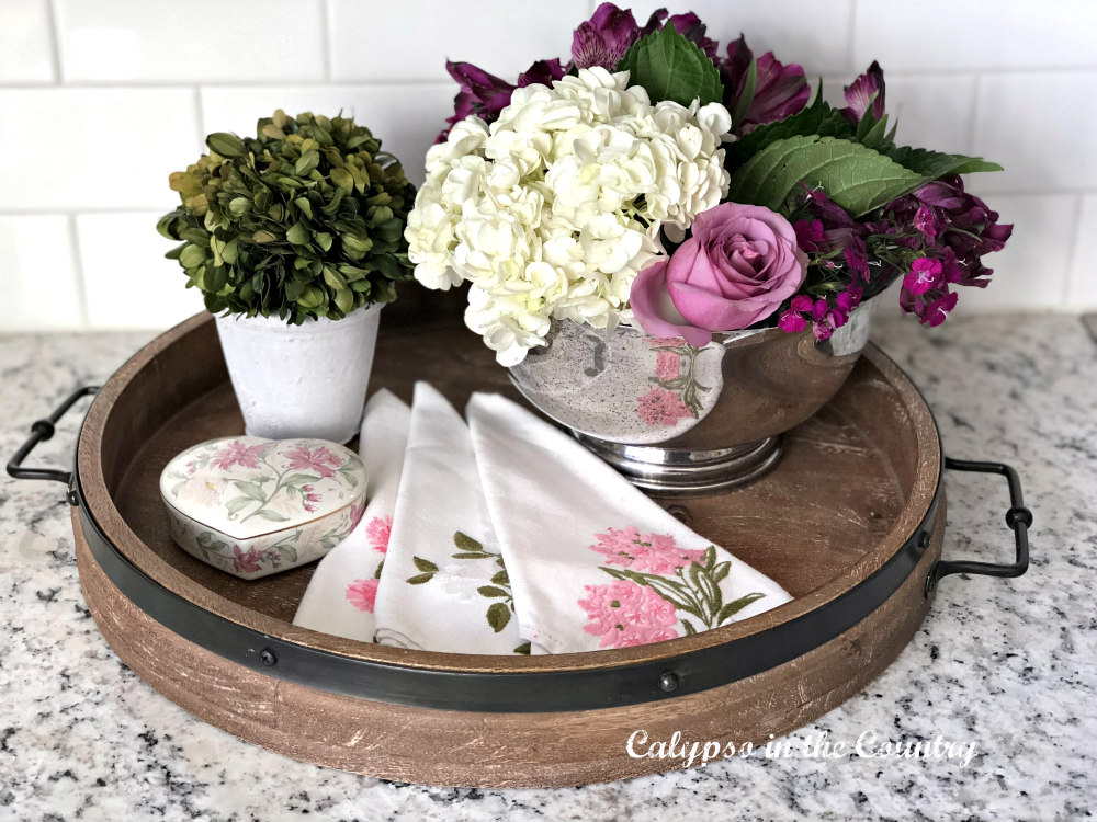 flowers and napkins on rustic wood tray