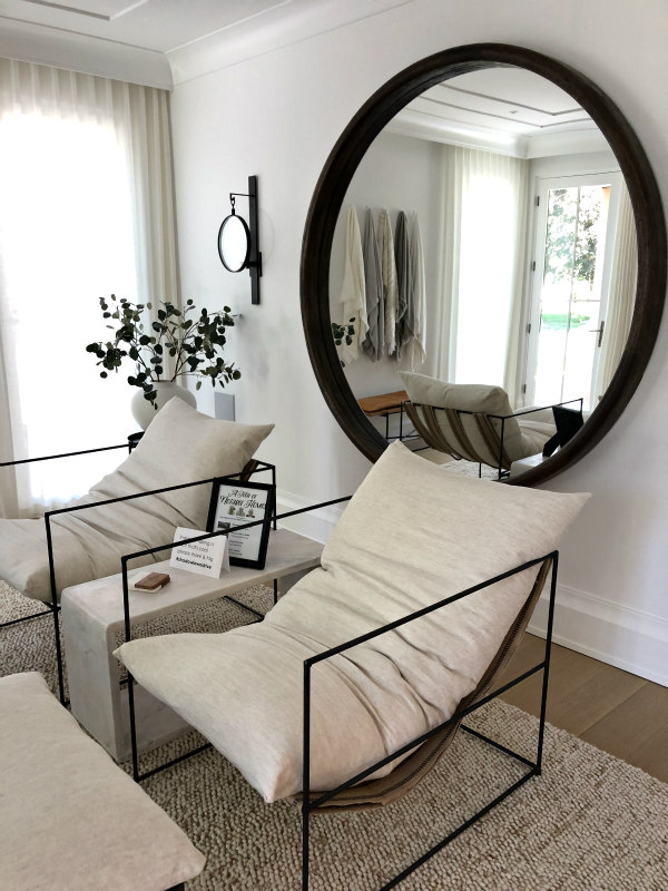 round mirror and lounge chairs