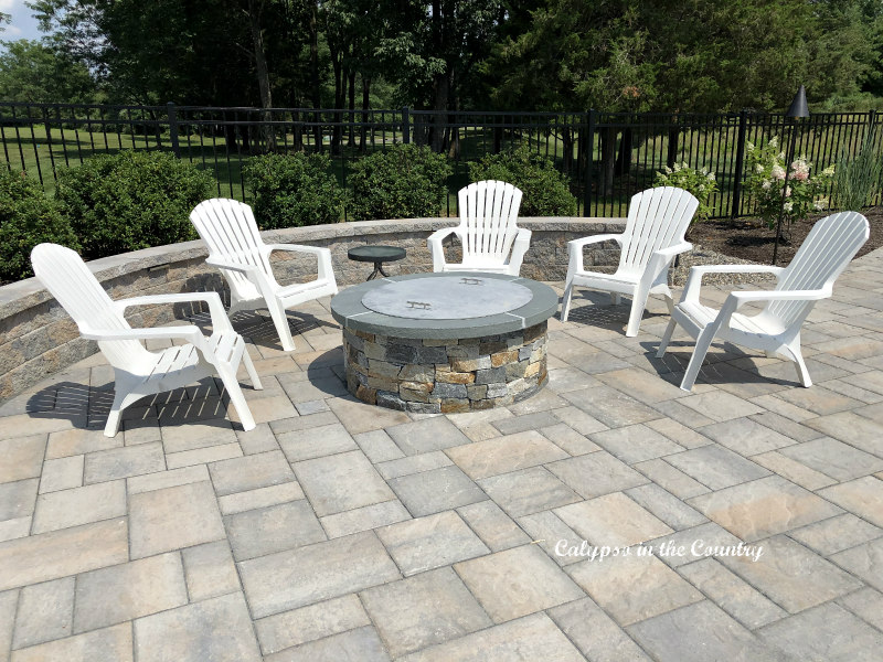 Summer entertaining at the stone fire pit with white adirondack chairs