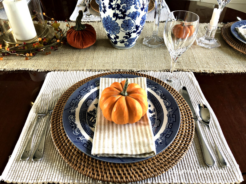 Orange pumpkin on blue and white plate for fall