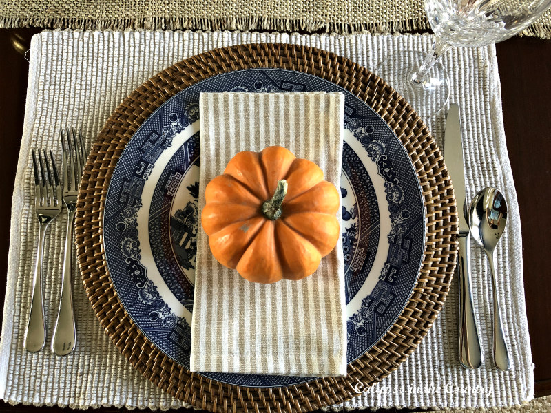 Blue and white place setting with orange pumpkin for fall