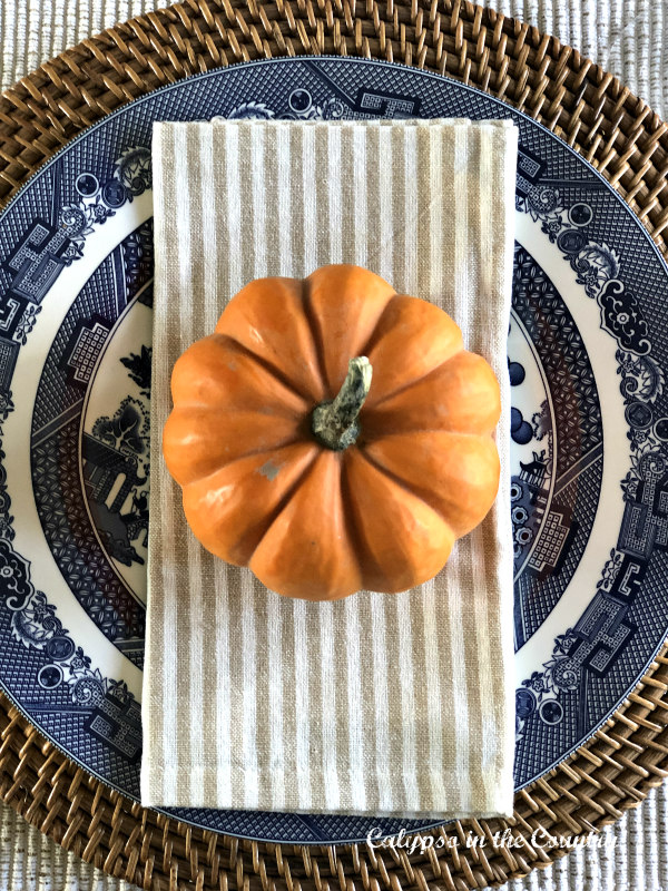 Orange pumpkin on blue and white place setting - Embracing Fall in the Dining Room