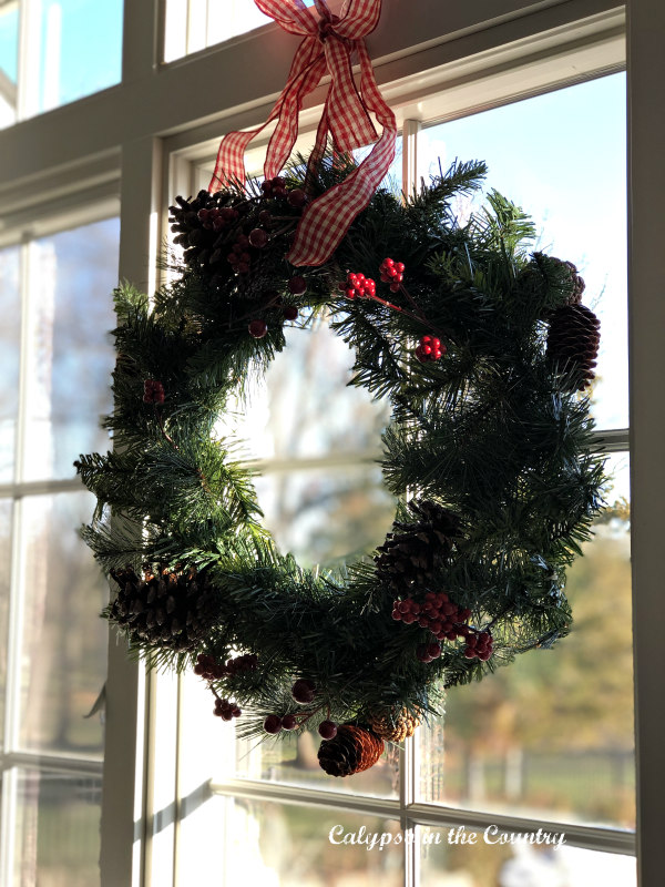 Christmas wreath in window with a red checked ribbon