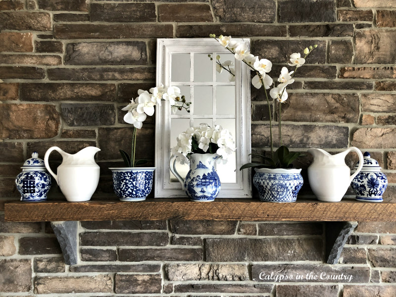 blue and white accessories for spring on rustic stone fireplace