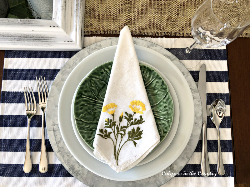 Floral napkin on blue and green spring place setting