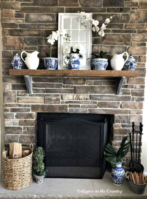 Rustic stone fireplace with blue and white accessories on mantel