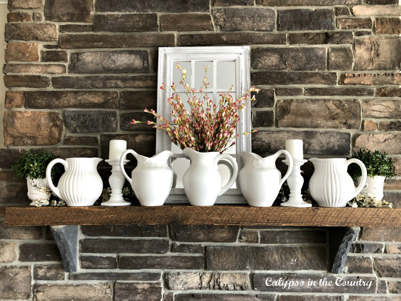 white pitchers on rustic farmhouse style mantel