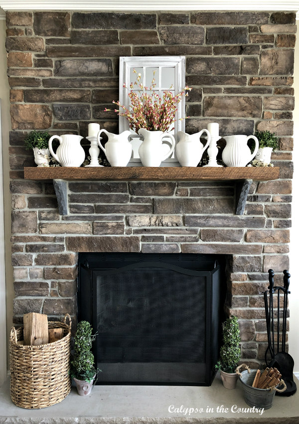 stone fireplace with white pitchers on mantel