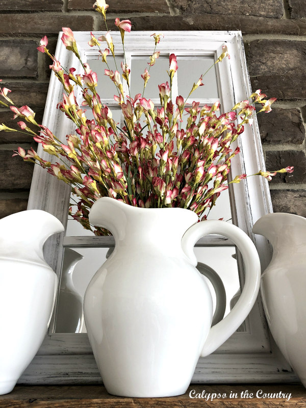 White farmhouse pitcher with flowers on mantel