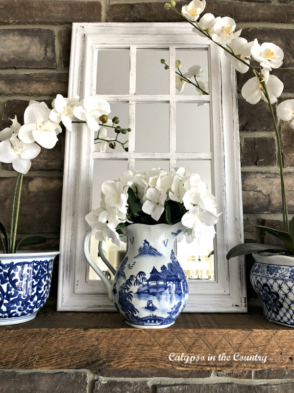 window pane mirror on mantel with blue and white accessories