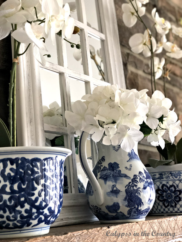 Blue and white accessories on fireplace mantel