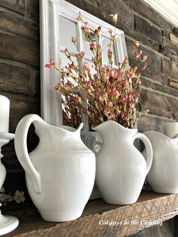 White pitchers and flowers on spring mantel