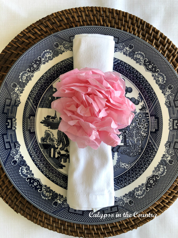 Pink DIY tissue paper flower napkin ring on blue and white plate