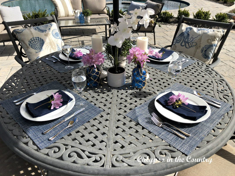 Patio table with blue and white place settings - entertaining ideas for outdoor spaces