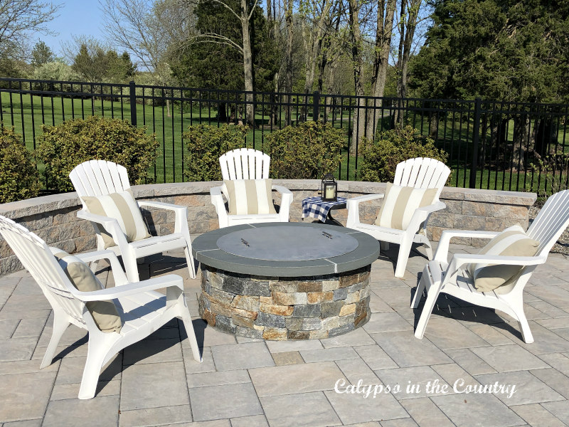 Stone Firepit with white adirondack chairs - cozy ideas for outdoor spaces