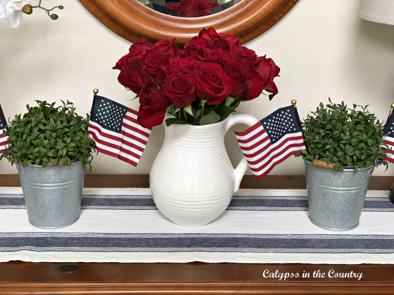 Red roses in white pitcher with flags - simple 4th of July decorating ideas