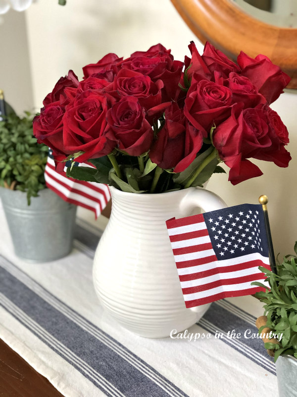 Red Roses and Flags - 4th of July decorating ideas for the foyer. #4thofjuly #4thofjulydecor #patrioticdecor #americanflags