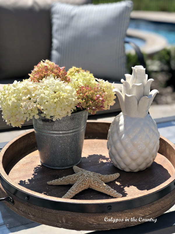 Hydrangeas in galvanized bucket on round tray - ideas for decorating with flowers