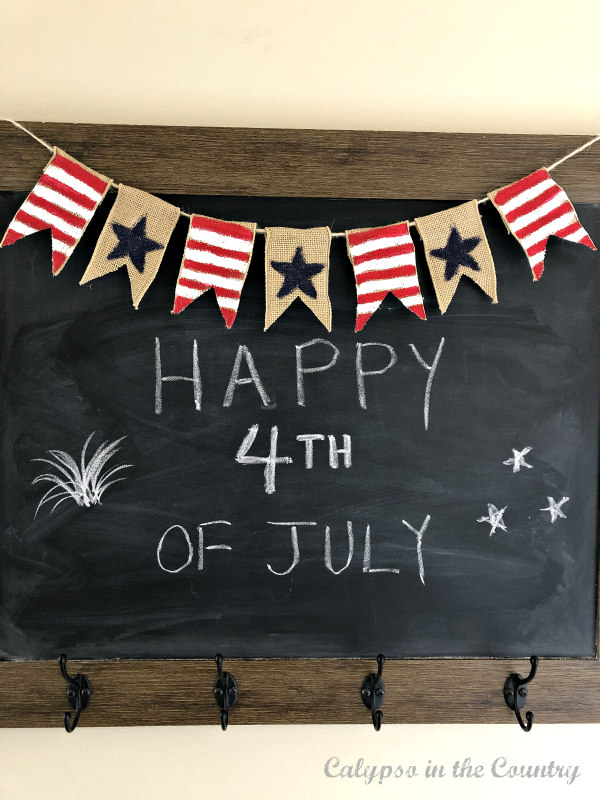 Happy 4th of July on chalkboard with red white and blue burlap banner.