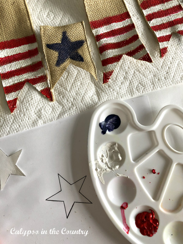 Red, White and Blue paint for a DIY patriotic banner. - How to decorate for the 4th of July on a budget. #4thofjuly #paintprojects #DIYdecor