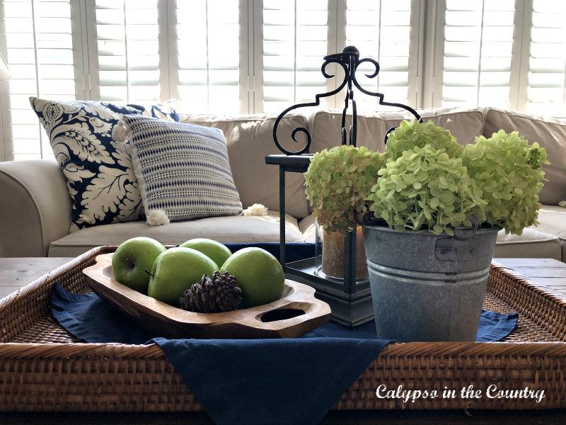 Coffee table vignette - green hydrangeas and apples on rattan tray - fall decor ideas