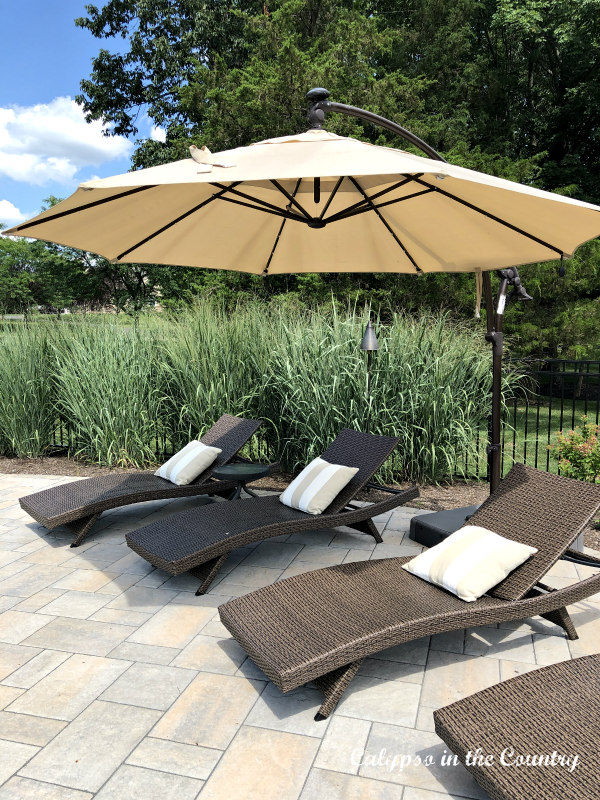 Outdoor wicker chaise lounge chairs with cantilever umbrella - backyard staycation ideas