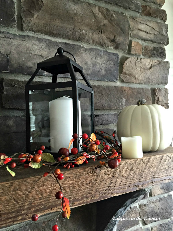 Candles and white pumpkins on rustic fireplace mantel for fall