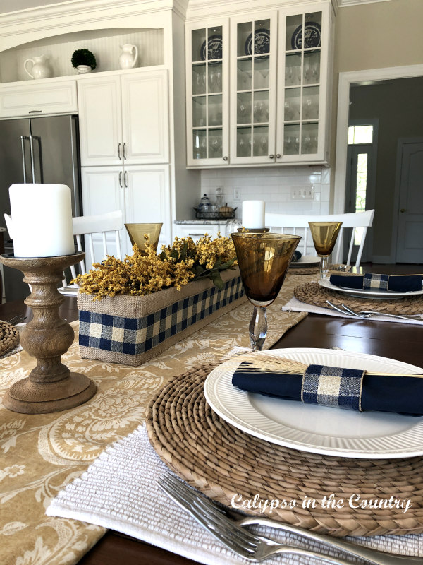 Gold and blue casual fall table setting ideas in a white kitchen
